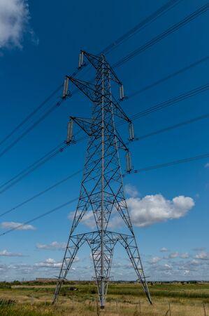 Overhead electricity power cables on a pylon against a blue sky