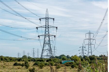 Multiple rows of overhead line power pylons in the countryside Stockfoto