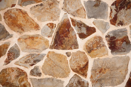 Close up of stone wall with brown and grey irregular shaped blocks cemented together Imagens