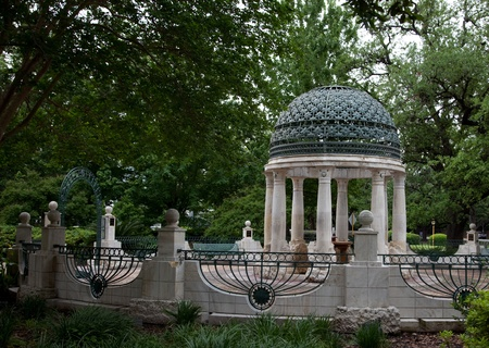 A memorial rotunda with marble columns and a green painted metal dome roof, surrounded by a low wall with railings and trees 6
