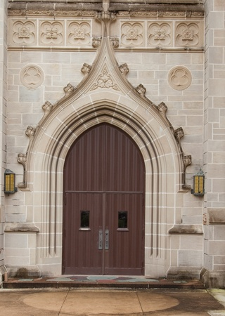 An ornate archway and wooden door of a stone church