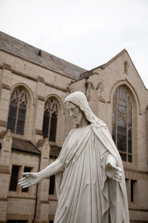 Cloase up of a marble statue of Jesus with arms outstretched and church in background