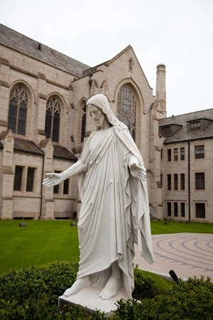 A marble statue of Jesus in front of a church tower