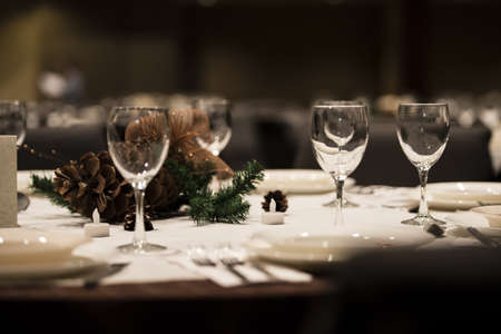 A dinner table setting for the fall showing cutlery and pine cones  Stock fotó