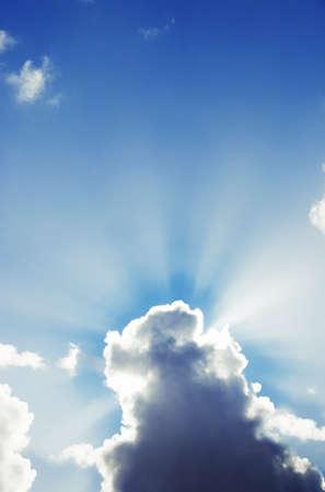 breaking out: Nubes blancas con una r�faga de sol que se rompe a cabo desde detr�s Foto de archivo
