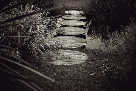 black boards: stepping stones over pond black and white