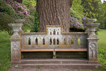 풍만한 집의 경내에있는 화려한 오래된 석재 좌석 스톡 콘텐츠