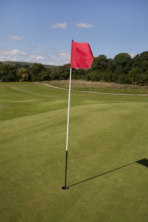 Red Golf Flag and Hole on a Golf Course Green Stock Photo