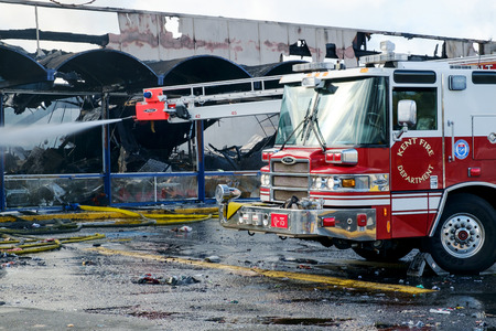 Kent, WA, USA November 14, 2016: Remotely operated boom on Pierce Sky-Boom fire engine from Kent Fire Dept spraying water at scene of commercial building fire in Kent, WA