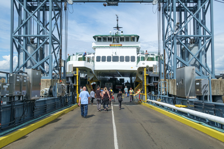 fv: Vashon Island, WA, USA August 8, 2016: Walk-on passengers walking down loading ramp to board ferry boat. FV Issaquah ferry loading at Vashon Island, Washington