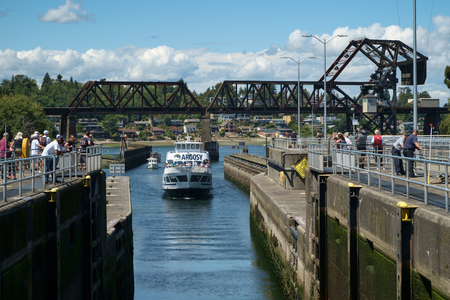 Seattle, USA July 20, 2016: Tour boat crowded with tourists enters Hiram Chittenden (Ballard) Locks. Tourist gather at locks to watch tour boat Redakční