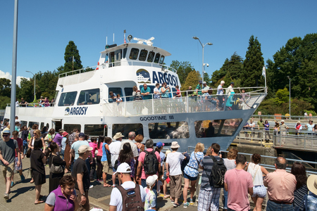 Seattle, USA July 20, 2016: Tour boat crowded with tourists enters Hiram Chittenden (Ballard) Locks. Tourist gather at locks to watch tour boat be lifted.
