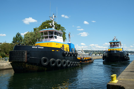 SEattle, USA July 20, 2016: Gulf Titan and Ocean Titan two Titan Class ocean going tug boats operated by Western Towboat Co. Two blue and yellow tugboats entering Hiram Chittenden (Ballard) Locks Editorial