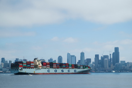 elliot: Seattle, USA August 1, 2016: Overseas container ship Cosco Europe arrives in Seattle. Small pleasure boat motoring near large container ship, Seattle skyline in background