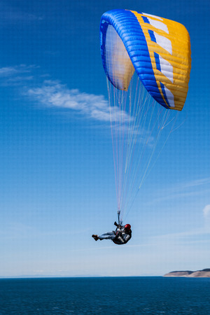 Man riding yellow and blue parasail over puget sound Parasail flyby Stok Fotoğraf