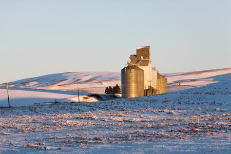 Grain silos on snow covered rolling hills of the Palouse region of Washington, USA Stock Photo