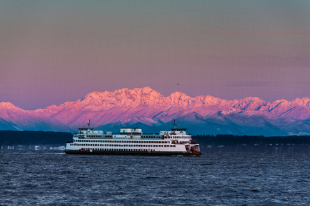 Seattle, USA February 25, 2011: Washington State Ferry crossing Puget Sound in winter with dawn alpenglow on Olympic Mountains background