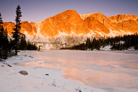 marie: Dawn lights up Diamond Peak rising above frozen Lake Marie in the Medicine Bow Mtns of Wyoming, USA