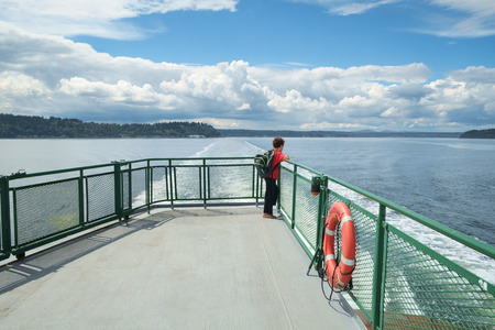 fv: Seattle, USA August 8, 2016: Young boy wearing orange shirt and backpack looks out onto Puget Sound from deck of ferry boat