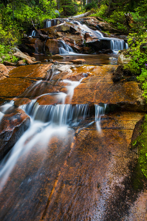 Small cascade of the Paradise River in Mt. Rainier National Park flows over smooth rocks
