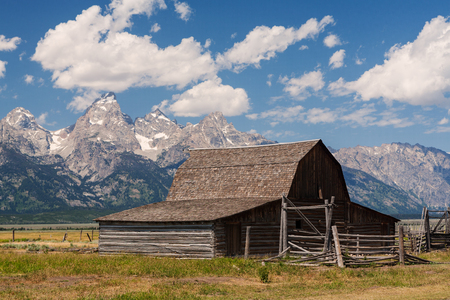 Abandoned wood barn under blue sky and puffy clouds on Mormon Row in Grand Teton National Park near Jackson Hole, Wyoming