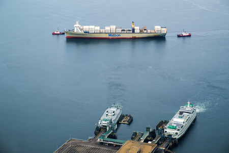 Seattle, USA May 20 2016: Two tugs from Crowley Maritime guide a container ship from Matson Shipping into the Harbor Island terminals. Two ferries at Coleman Dock