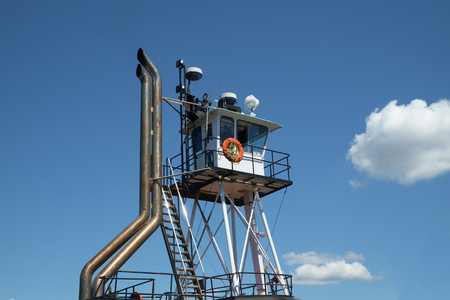 Elevated wheelhouse of pusher style tugboat with steel exhaust stacks and orange life ring.
