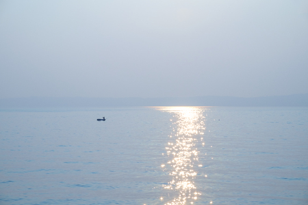 Small fishing boat with single person fishing the waters of Puget Sound, Washington at sunset