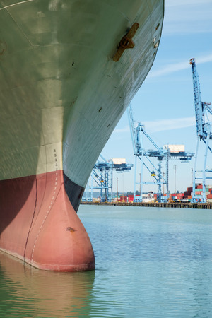 Bow of large container ship with bulbous bow feature above water line and dock cranes in background Stock Photo