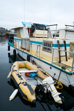 An older, well maintained house boat with inflatable dingy with an outboard motor on calm waters in marina at Fishermens Terminal in Seattle, Washington