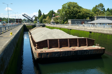Seattle, USA July 20, 2016: Barge loaded with sand and gravel tied up in Hiram Chittenden (Ballard) Locks. Elevated wheelhouse of pusher tugboat allows clear view over barge Stock Photo - 118177733