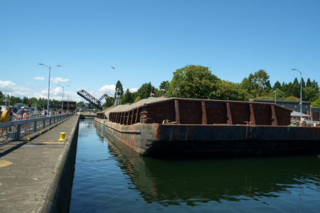 Seattle, USA July 20, 2016: Barge loaded with sand and gravel tied up in Hiram Chittenden (Ballard) Locks. Elevated wheelhouse of pusher tugboat allows clear view over barge