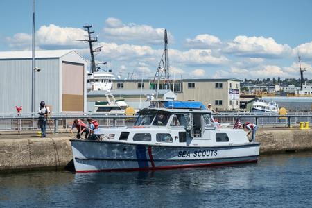 Seattle, USA July 20, 2016: Sea Scouts bring boat into Ballard Locks. Sea Scouts learning boating skills while tying up at Hiram Chittenden (Ballard) Locks Sajtókép