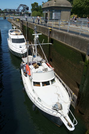SEATTLE, WASHINGTON, USA JULY 7, 2017: Two white pleasure boats enter the small lock at Hiram Chittenden Locks (Ballard Locks) in Seattle, Washington to be lifted up from Puget Sound to Salmon Bay