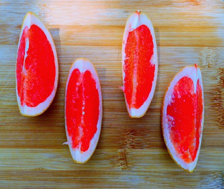 Grapefruit wedges lying on wooden table