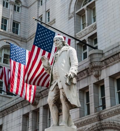 Benjamin Franklin in front of American flags.