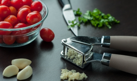 A garlic press with bright red tomatoes in a bowl photo