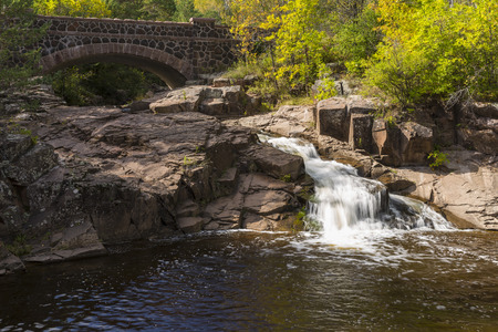 amity: Stone Arch Bridge and Waterfall In Autumn Stock Photo