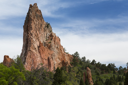 rock formation: A rock formation extending above the trees.
