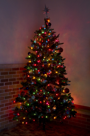 lighted: A lit Christmas tree in a corner of a room.