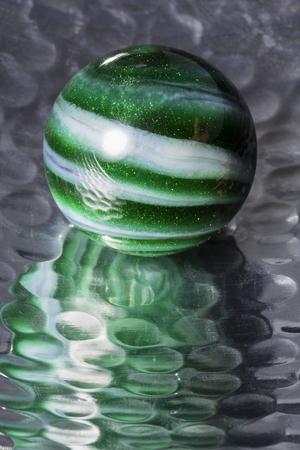 Green Swirl Marble In Reflective Bowl 版權商用圖片