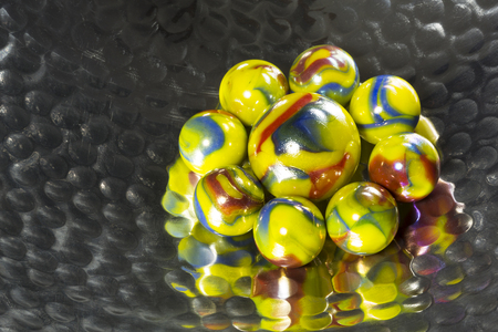 Colorful Swirl Marbles In Reflective Bowl