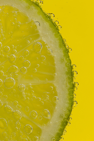 Lime Fruit in clear soda with yellow background