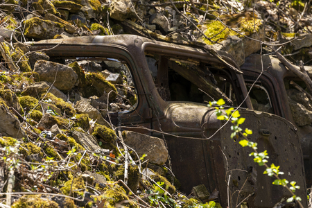 Old cars buried in the side of a hill for erosion control. Banco de Imagens