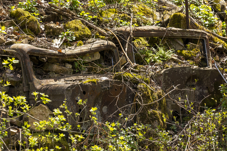 Old cars buried in the side of a hill for erosion control. Stok Fotoğraf