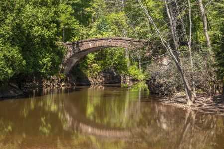 Stone Arch Footbridge Over Creek In The Woods