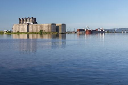 An industrial shipping harbor with grain silos and a ship being loaded with coal.