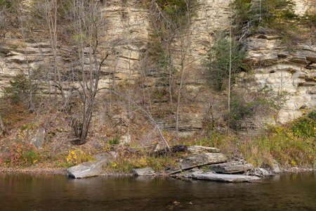 Root River In Autumn - A scenic river next to a cliff.