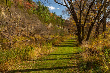 A hiking trail in the woods along a river in autumn.