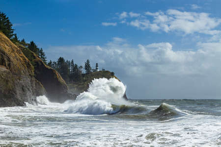 Cape Disappointment Lighthouse with a crashing wave. 版權商用圖片